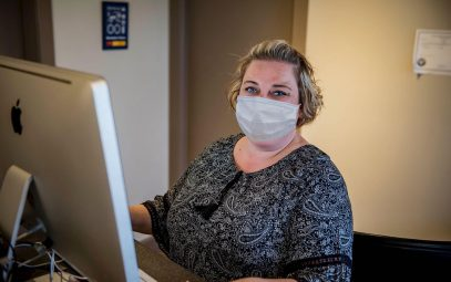 Woman wearing mask at the front desk of mechanic shop