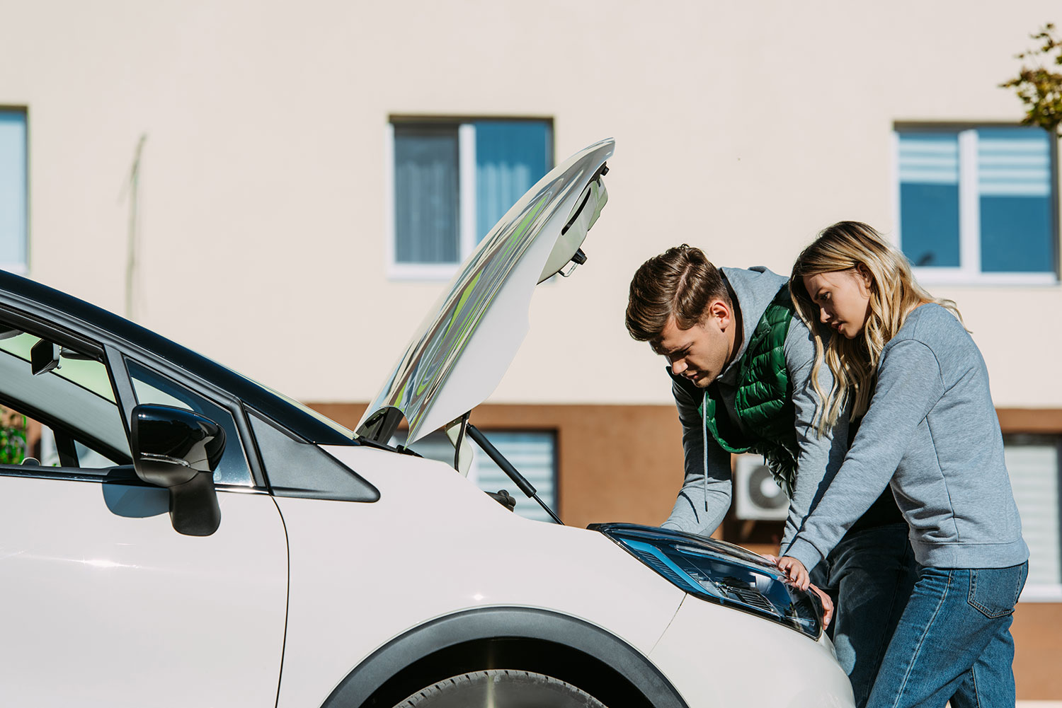 Young couple examining a car engine.