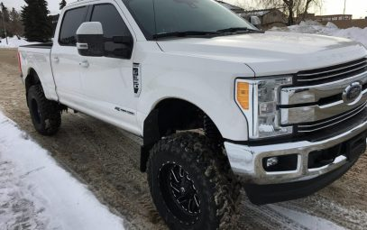 A white Ford diesel truck in winter